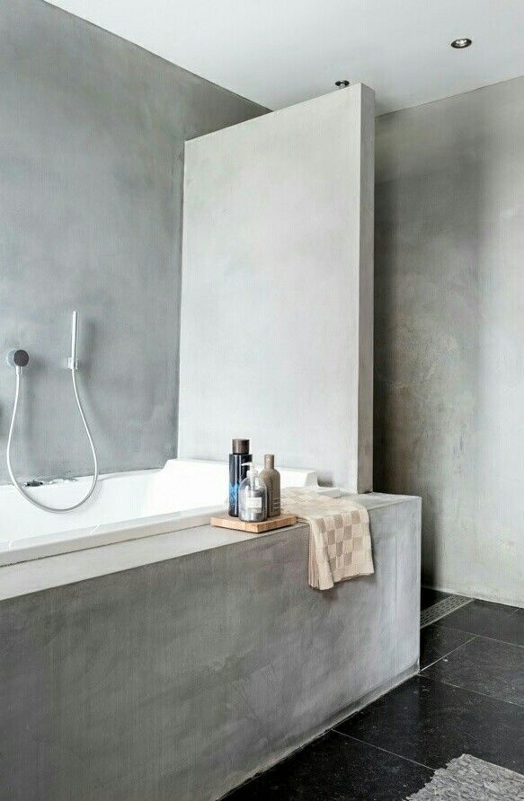 a minimalist industrial bathroom fully done with concrete, with a half wall and with black tiles on the floor is practical