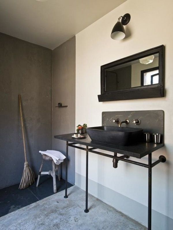 a modern industrial bathroom with a concrete floor and walls, a black sink on a vanity, a mirror and a wall sconce