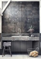 a minimalist industrial bathroom done with rusty tiles, concrete and sleke wooden surfaces, exposed pipes and wooden stools
