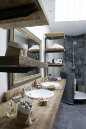a vintage industrial bathroom with white walls, concrete tiles, rough wooden shelves and a vanity plus a large mirror