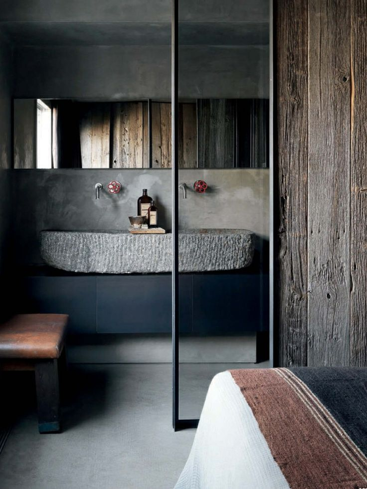 a modern industrial bathroom with concrete and rough wood walls, a large carved stone sink, a long mirror and a leather bench