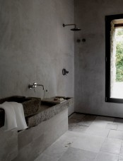 a minimalist industrial bathroom done with concrete and tiles, stone sinks, exposed pipes and a large window for a view