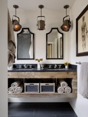 a rustic industrial bathroom with a floating rough wood vanity with an open storage, pendant lamps, a duo of mirrors and some artworks is very elegant
