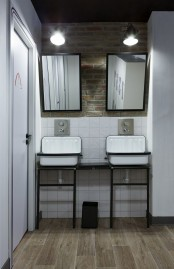a modern industrial bathroom with white tiles, a brick wall, a wooden floor, vintage sinks on a stand and a duo of mirrors