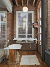 a vintage industrial bathoom with brick walls, a double sink, a metal clad bathtub and pendant lamps is very chic