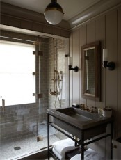 a moody vintage bathroom with industrial touches, grey tile and beadboard walls, a stone sink on a stand, pendant lamps and a window in the shower