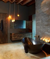 a mascauline meets industrial bathroom with concrete and faux stone walls, rough wooden furniture and a door, a polished stone bathtub and candles and pendant lamps
