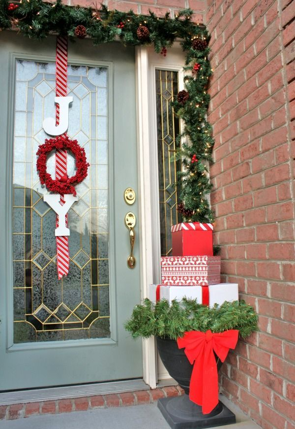 an evergreen garland with pinecones and lights, a letter sign in red and an urn with a stack of Christmas gift boxes