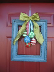 a front door Christmas wreath made of a blue frame with colorful ornaments and a green silk bow is a whimsy and cool idea