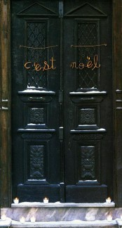 lots of candles in glasses and letters placed on the doors compose a simple and stylish decoration for the front door