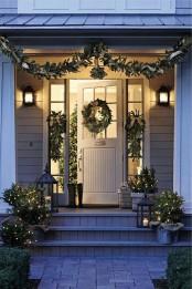 natural front door Christmas decor with an evergreen garland and posies, a wreath and evergreens in buckets with lights