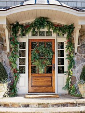 simple and natural Christmas front door styling with an evergreen garland with red blooms and a matching large wreath on the door