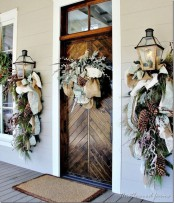 chic natural front door styling with mesh and burlap ribbons, evergreens, pinecones, berries, and whitewashed evergreens on the door