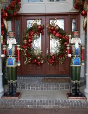 whimsical Christmas front door styling with evergreens, ornaments, gilded leaves and red ribbons plus giant nutcrackers on front of the door
