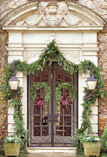 elegant natural Christmas styling with an evergreen garland that frames the entrance, evergreen wreaths with purple bows