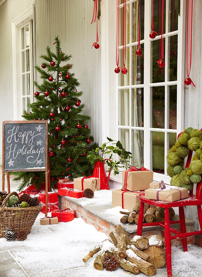 a red and green Christmas front door styled with a Christmas tree with red ornaments, red ornaments hanging down, gift boxes, firewood and a basket with pinecones and yarn balls
