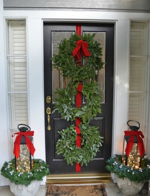 chic Christmas front door styling with evergreen wreaths and a red ribbon, lanterns with lights and red bows plus evergreens