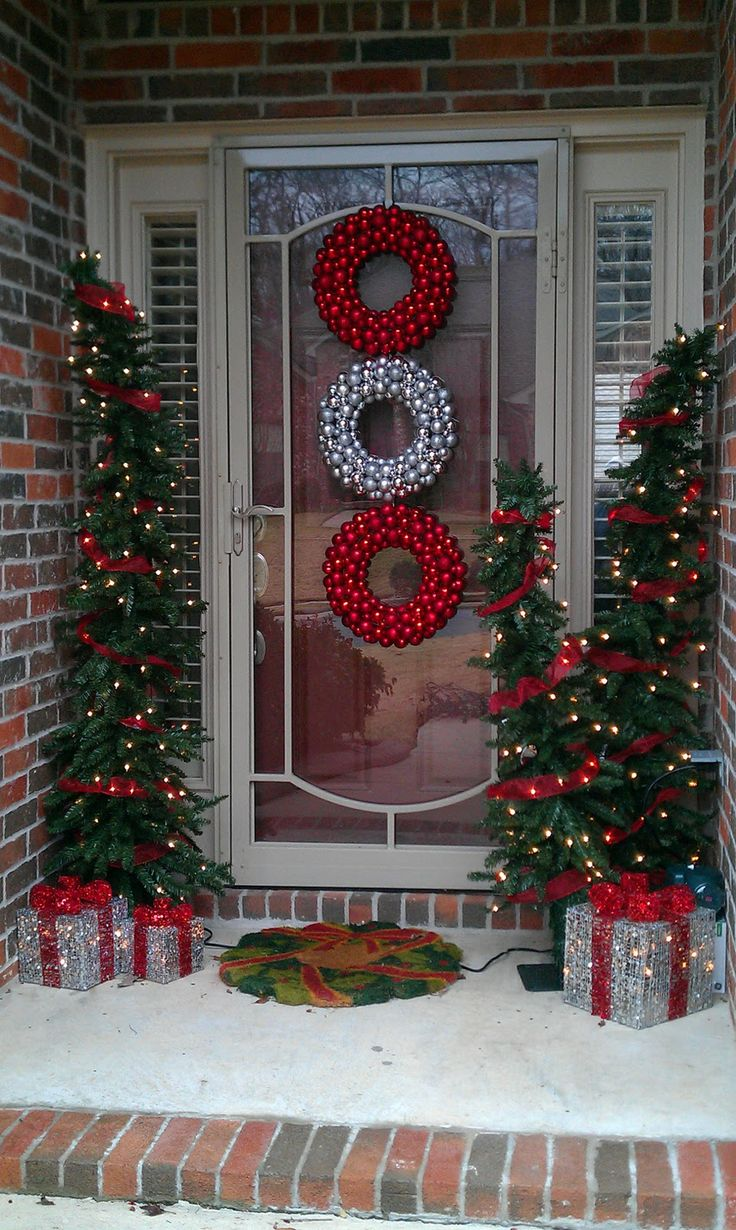 cozy front door Christmas styling with red and silver Christmas ornament wreaths, tree Christmas trees with red ribbons and lights, silver lit up gift boxes