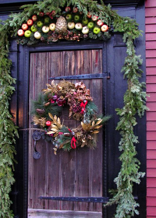 Christmas front door decor with an evergreen garland, pinecones, apples and a quirky wreath with pinecones, apples, dried leaves and berries