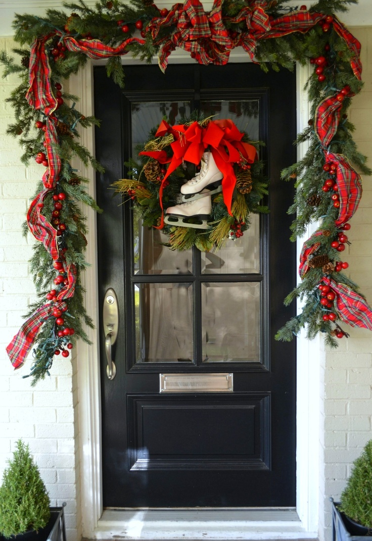 chic front door Christmas styling with an evergreen garland with pinecones and apples, plaid ribbons and skates with a bow instead of a wreath