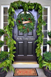 Christmas front door styling with an evergreen garland, a Christmas wreath of greenery, berries and pinecones