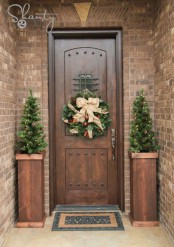 rustic front door Christmas styling with mini tree with pinecones and lights and a wreath with pinecones, ornaments and a bow on top