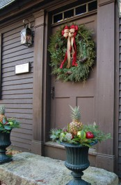 creative front door styling with an evergreen wreath with pinecones and bows plus urns with pineapples and fruits for a whimsy touch