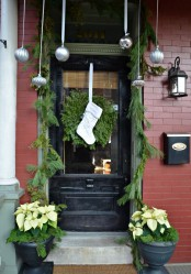 natural Christmas front door decor with hanging silver ornaments, an evergreen garland and wreath with a stocking and an urn with neutral blooms