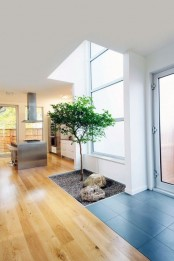 a mini courtyard indoors with pebbles, rocks and a small tree by the window is a cool and fresh idea