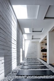 a minimalist indoor courtyard with white pebbles and black planks over them plus skylights is a fresh design solution
