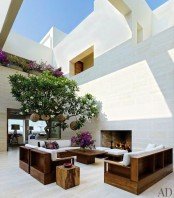an indoor courtyard with a whole living room and some trees growing here is a cozy and private idea