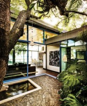 some plants, a pond with fish and large trees in the inner terrace of the house create an oasis of relaxation