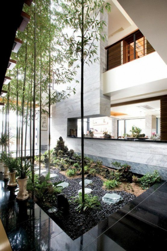 a spectacular indoor courtyard with black pebbles, growing and potted greenery and some tall trees that highlight the double-height ceilings