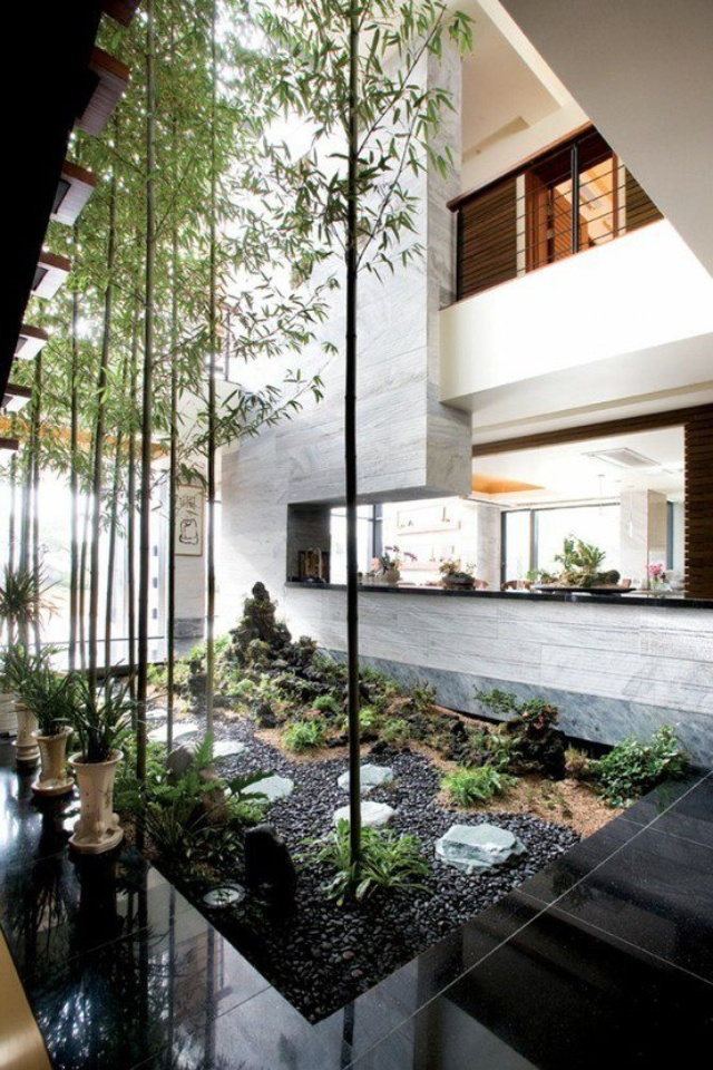 a spectacular indoor courtyard with black pebbles, growing and potted greenery and some tall trees that highlight the double height ceilings