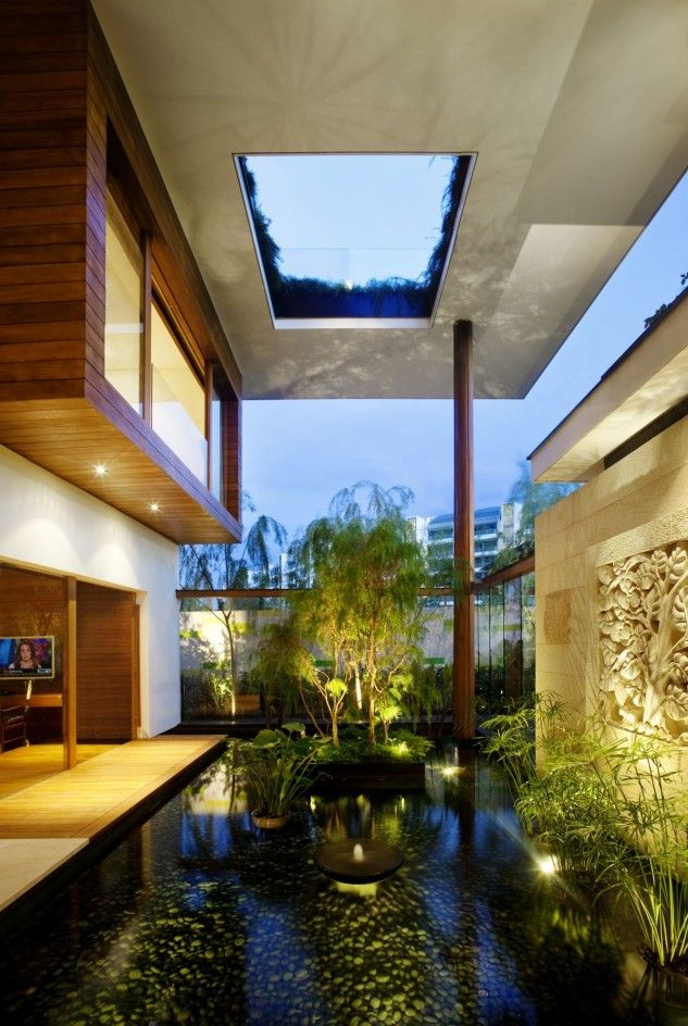 a whole water garden indoors   with a pond, lots of plants, artworks and some lights to accent it is a very zen space