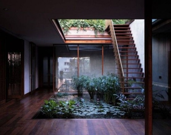 an indoor courtyard with a pond with lots of plants and a skylight over it for a fresh and modern look