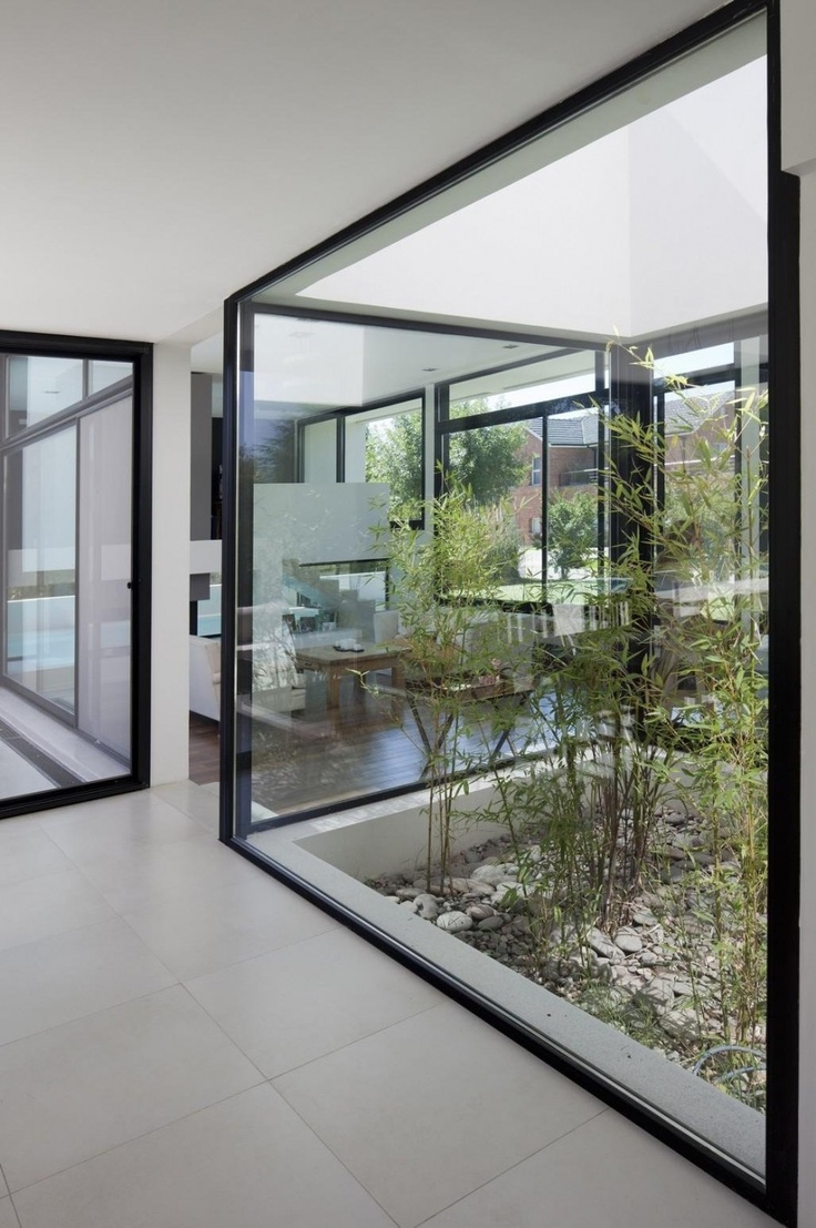 a mini indoor courtyard with pebbles and greenery growing here under a skylight that has decorative value and brings life here