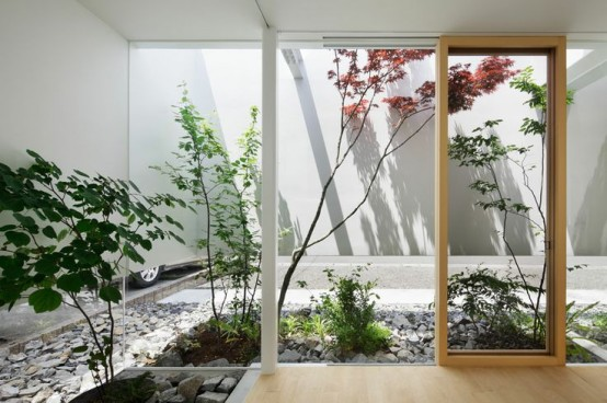 a stylish skylit indoor courtyard with pebbles and rocks and some plants growing here is a cool idea
