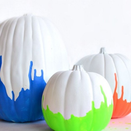 white pumpkins spruced up with neon green, blue and orange touches are a very fresh and bold idea for Halloween decorating