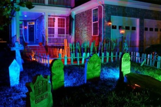 a mini graveyard in front of the house with neon lights is a great idea to style your outdoor space for Halloween