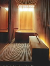 a Japanese minimalist bathroom clad with light stained wooden slabs, with a wooden bathtub nand a creative vanity with a sink plus a skylight