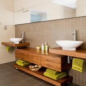 a modern bathroom clad with tan and brown tiles of various sizes, rich stained wooden vanities and a storage unit, bright towels