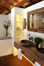 a tropical bathroom with a built-in wooden vanity, stone sinks, built-in niches for storage, a mirror in a rough wooden frame