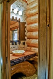 a wooden bathroom clad with wooden logs, a rough wood vanity and a stone accent wall is a lovely idea to rock