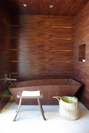 a rich stained wood clad bathroom with a matching bathtub, a small stool and a basket plus a niche for storage