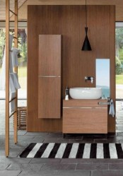 a contemporary bathroom with sleek wooden furniture for storage, a modern bowl sink, a black pendant lamp and a ladder plus a striped rug