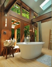 a modern bathroom with a light stained wall and a laminate floor, a rich stained wall and matching beams is a very elegant space with much natural light