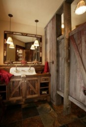 a rough wooden bathroom clad with reclaimed wood and with a matching vanity, with vintage pendant lamps and bold red towels