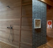 a sleek bathroom with a wood clad wall, a ladder, a wooden slab floor is a cool idea for a contemporary space