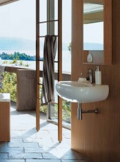 a bathroom with a view, with a wooden ladder, wood clad walls, a sink, a mirror cabinet in a wooden frame and a wooden stool